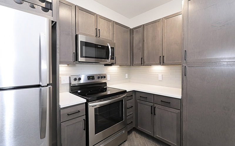 Spacious and well lit kitchen with wood floors and stainless steel appliances.