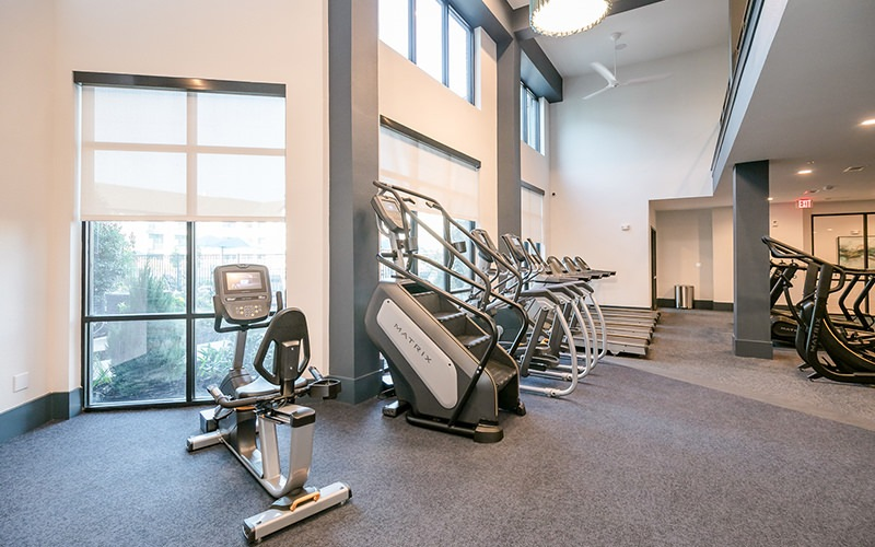 Large well lit gym with large windows and ample workout equipment